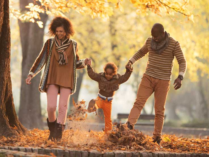 Family walking holding hands kicking leaves